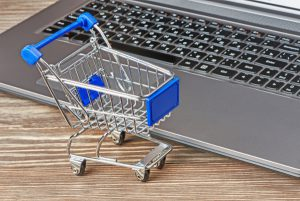 Shopping cart and laptop on table